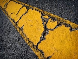 Closeup of yellow line on cracked asphalt.